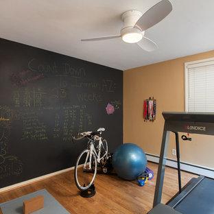 Idee per una sala pesi stile americano di medie dimensioni con pareti gialle e pavimento in legno massello medio
