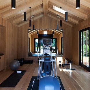 Esempio di un'ampia sala pesi minimal con pareti marroni, parquet chiaro e pavimento marrone