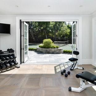 Esempio di una sala pesi chic con pareti bianche, parquet chiaro e pavimento beige