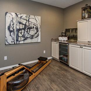 Immagine di una palestra multiuso tradizionale di medie dimensioni con pareti grigie, pavimento in legno massello medio e pavimento marrone