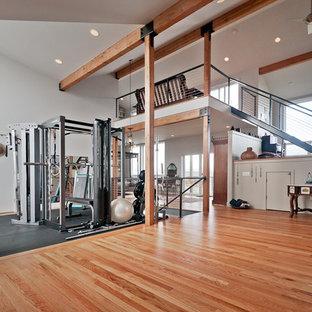 Ispirazione per una grande sala pesi design con pareti bianche e pavimento in legno massello medio