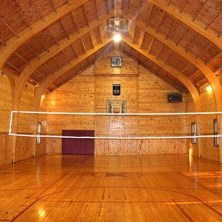 Immagine di un ampio campo sportivo coperto country con pareti marroni, pavimento in legno massello medio e pavimento marrone