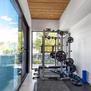 Foto di una piccola palestra in casa contemporanea con pareti bianche, pavimento in cemento e pavimento bianco
