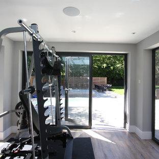 Foto di una palestra design con pareti grigie e pavimento in compensato