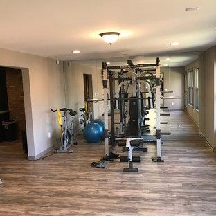 Idee per una sala pesi classica di medie dimensioni con pareti bianche e pavimento in legno massello medio
