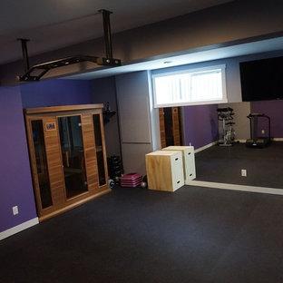 Foto di una grande sala pesi moderna con pareti viola