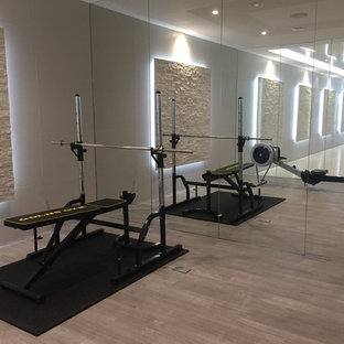 Photo of a large contemporary home gym in Surrey with beige walls, vinyl flooring and beige floors.