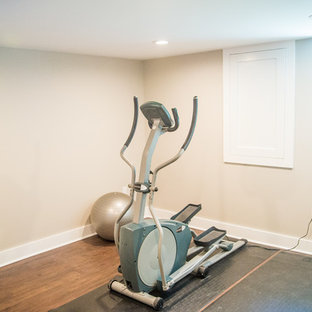 Foto di una sala pesi minimal di medie dimensioni con pareti beige e pavimento in legno massello medio