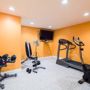 Foto di una sala pesi classica di medie dimensioni con pareti arancioni e moquette