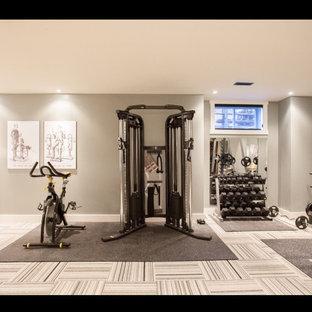 Modelo de sala de pesas minimalista, grande, con paredes grises y moqueta