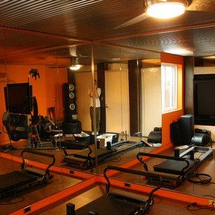 Moderner Fitnessraum mit oranger Wandfarbe und Korkboden in Sonstige