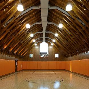 Landhaus Fitnessraum mit Indoor-Sportplatz, oranger Wandfarbe und hellem Holzboden in Providence
