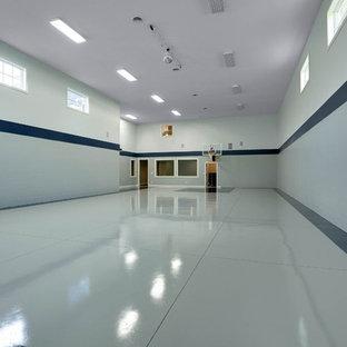 Immagine di un campo sportivo coperto country con pareti blu e pavimento in cemento