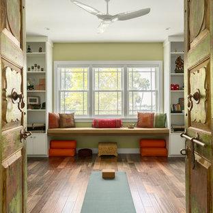 Immagine di uno studio yoga di medie dimensioni con pareti verdi, pavimento in legno massello medio e pavimento marrone