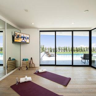 Mittelgroßer Klassischer Yogaraum mit weißer Wandfarbe, hellem Holzboden und beigem Boden in Orange County