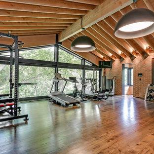 Ispirazione per un'ampia sala pesi american style con pareti rosse, parquet scuro e pavimento marrone