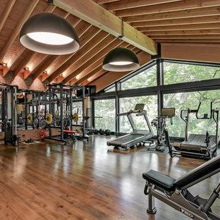 Foto di un'ampia sala pesi american style con pareti rosse, parquet scuro e pavimento marrone