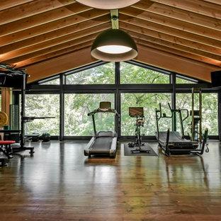Idee per un'ampia sala pesi stile americano con pareti rosse, parquet scuro e pavimento marrone