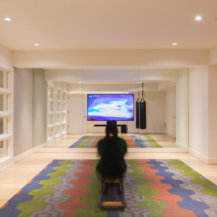 Home yoga studio - mid-sized modern light wood floor home yoga studio idea in DC Metro with white walls