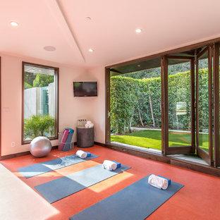 Inredning av ett modernt mellanstort hemmagym med yogastudio, med vita väggar och rött golv