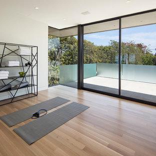 Esempio di uno studio yoga minimal di medie dimensioni con pareti bianche, parquet chiaro e pavimento marrone