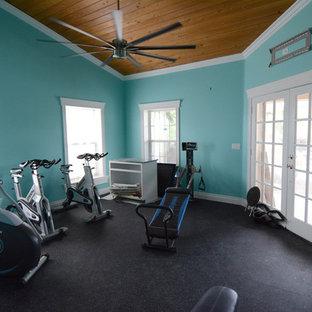 マイアミの広いトランジショナルスタイルのおしゃれな多目的ジム (青い壁、黒い床) の写真