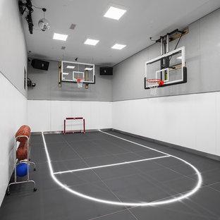 Immagine di un ampio campo sportivo coperto contemporaneo con pareti grigie e pavimento grigio