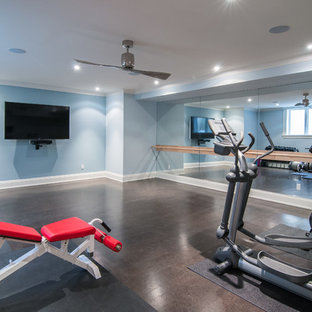 This is an example of a large traditional multipurpose gym in Other with blue walls and dark hardwood floors.