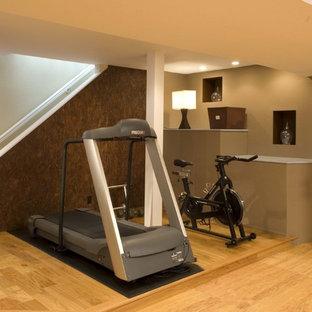 Moderner Fitnessraum mit beiger Wandfarbe, hellem Holzboden und gelbem Boden in Denver