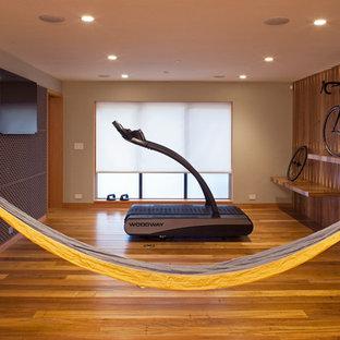 Esempio di una palestra multiuso contemporanea di medie dimensioni con pareti marroni, pavimento in legno massello medio e pavimento marrone