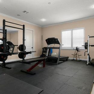 Multifunktionaler, Großer Mediterraner Fitnessraum mit oranger Wandfarbe und schwarzem Boden in Orlando