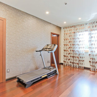 Foto di un piccolo studio yoga contemporaneo con pareti multicolore e pavimento in legno massello medio
