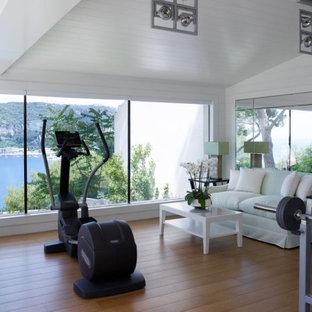 Foto di uno studio yoga minimal di medie dimensioni con pareti bianche, pavimento in legno massello medio, pavimento beige e soffitto a volta
