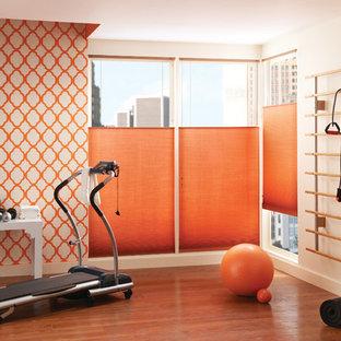 Multifunktionaler, Großer Moderner Fitnessraum mit oranger Wandfarbe, braunem Holzboden und orangem Boden in Sonstige