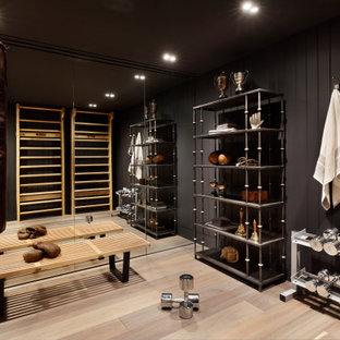 This is an example of a traditional home gym in London with grey walls, light hardwood flooring and beige floors.