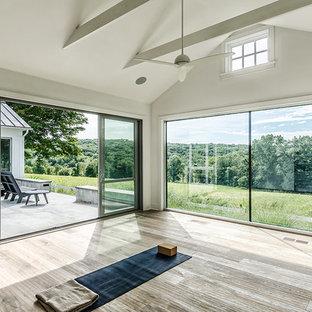 Mittelgroßer Country Yogaraum mit weißer Wandfarbe und hellem Holzboden in New York