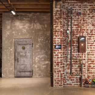メルボルンの巨大なコンテンポラリースタイルのおしゃれな多目的ジム (赤い壁、コンクリートの床、グレーの床) の写真