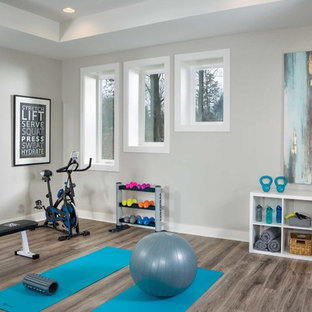 На фото: йога-студия среднего размера в морском стиле с полом из винила, коричневым полом и серыми стенами с