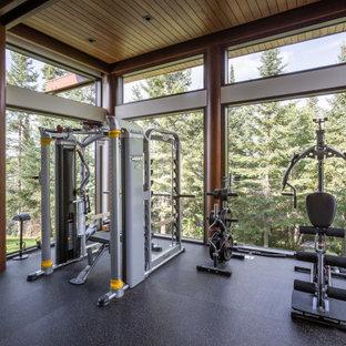 Rustikaler Fitnessraum mit schwarzem Boden und Holzdecke in Sonstige