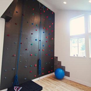 Großer Klassischer Fitnessraum mit Kletterwand, weißer Wandfarbe und hellem Holzboden in Seattle