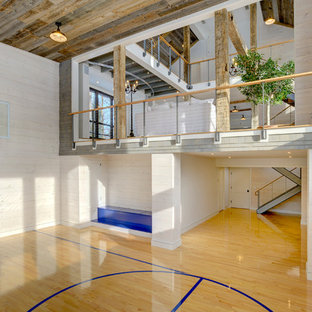 This is an example of an expansive farmhouse indoor sports court in Bridgeport with white walls and light hardwood flooring.