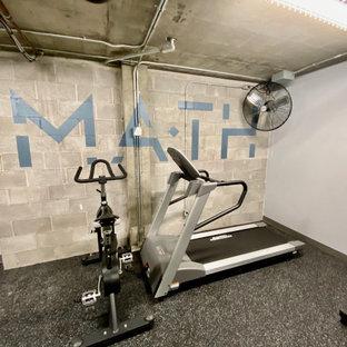 Immagine di una grande palestra multiuso industriale con pareti grigie, pavimento in cemento, pavimento grigio e travi a vista