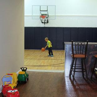 Großer Klassischer Fitnessraum mit Indoor-Sportplatz, weißer Wandfarbe und hellem Holzboden in Milwaukee
