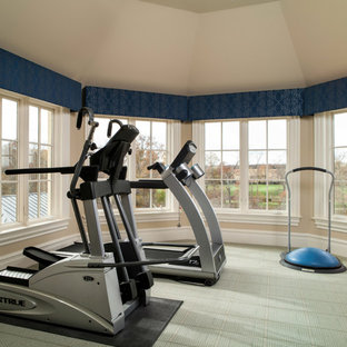 Inspiration for a traditional home gym in Charlotte with beige walls, carpet and green floors.