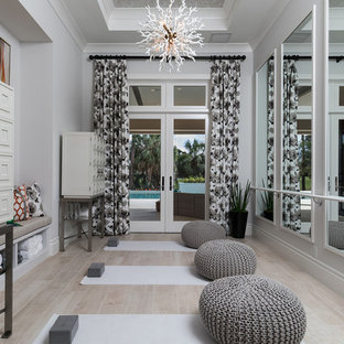 Mid-sized tuscan light wood floor and beige floor home yoga studio photo in Other with gray walls