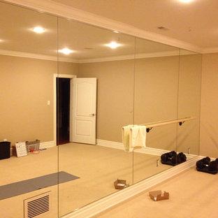 Inredning av ett mellanstort hemmagym med yogastudio, med beige väggar och heltäckningsmatta