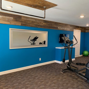Example of a large minimalist carpeted and brown floor home weight room design in Dallas with blue walls