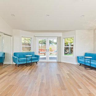 Foto di un grande studio yoga classico con pareti bianche, pavimento in legno massello medio e pavimento beige