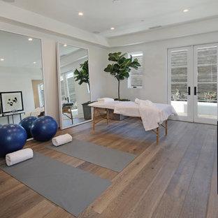 Klassischer Yogaraum mit weißer Wandfarbe, braunem Holzboden und braunem Boden in Los Angeles