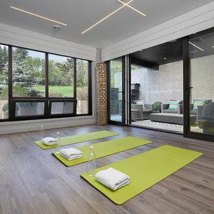 Foto di uno studio yoga minimal di medie dimensioni con pareti grigie e parquet chiaro